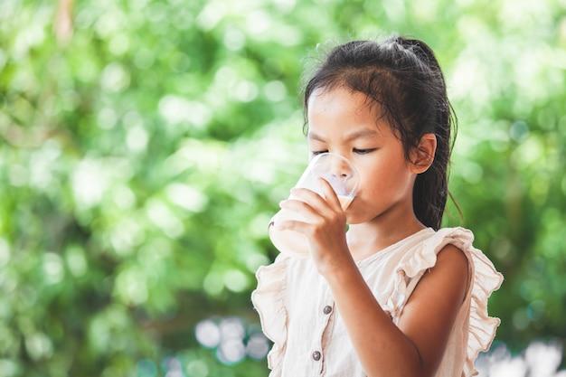 Nettes asiatisches kindermädchen trinkt eine milch vom glas Premium Fotos