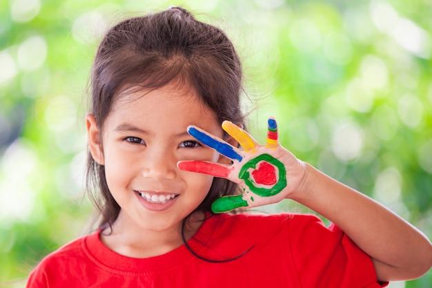 Nettes asiatisches kleines kindermädchen mit den gemalten händen lächelnd mit spaß und glück Premium Fotos
