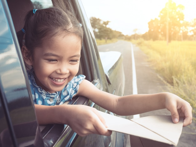 Nettes asiatisches mädchen des kleinen kindes, das spaß hat, mit spielzeugpapierflugzeug aus autofenster heraus zu spielen Premium Fotos