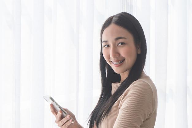 Nettes asiatisches mädchen mit klammern unter verwendung des handys durch morgenfenster Premium Fotos