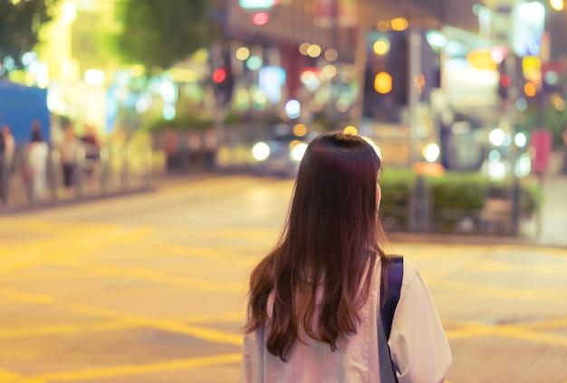 Nettes asiatisches reisendmädchen in der nachtstraße von hong kong Premium Fotos