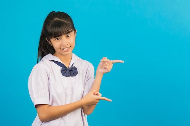 Nettes asiatisches schulmädchen, das zwei hände zeigen geste auf einem blau tut. Kostenlose Fotos