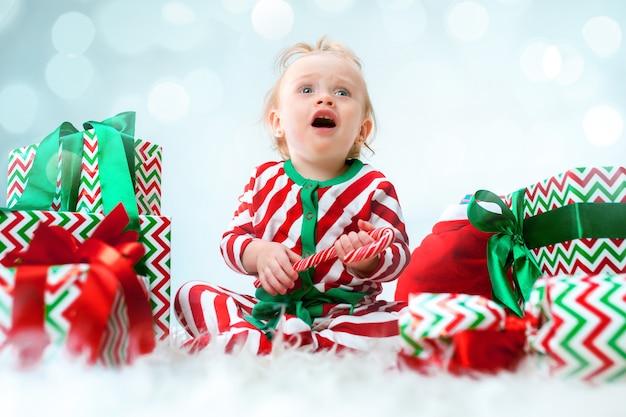 Nettes baby 1 jahr alt nahe weihnachtsmütze, die über weihnachten aufwirft Kostenlose Fotos