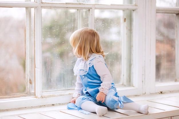 Nettes baby, das auf der fensterbank sitzt und aus dem fenster schaut Premium Fotos
