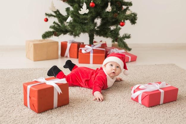 Nettes baby, das den weihnachtsmannanzug trägt, der auf boden neben weihnachtsbaum kriecht Premium Fotos