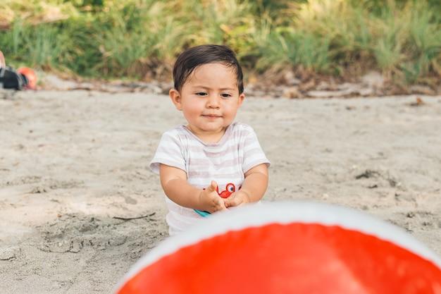 Nettes baby, das mit ball auf strand spielt Kostenlose Fotos
