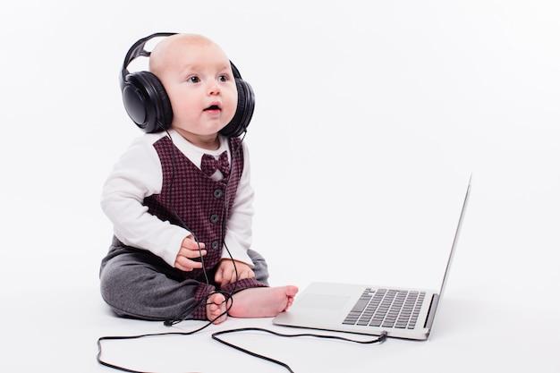 Nettes baby, das vor tragenden kopfhörern eines laptops sitzt Premium Fotos