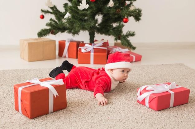 Nettes baby, das weihnachtsmannanzug trägt, der auf boden über weihnachtsbaum kriecht Premium Fotos