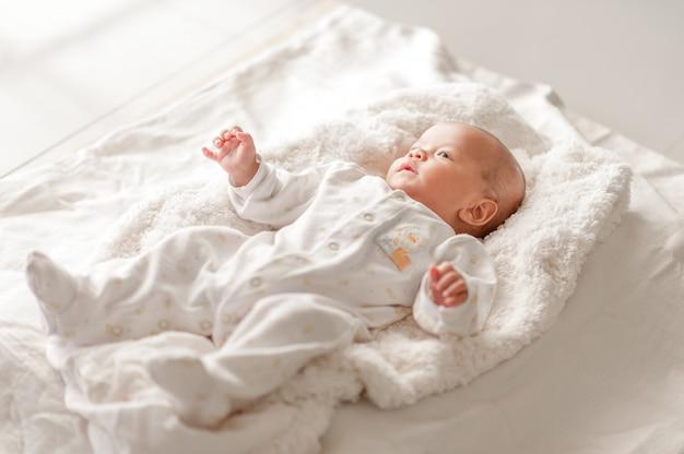 Nettes baby in einem schlafzimmer der weißen leuchte neugeborenes baby ist nett. Premium Fotos