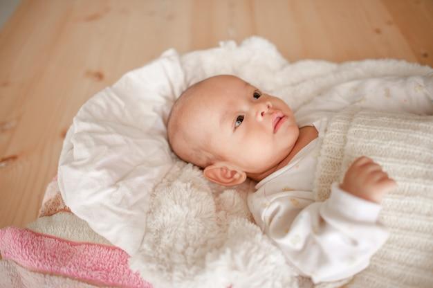 Nettes baby in einem schlafzimmer des weißen lichtes neugeborenes baby ist nett. in bettwäsche für kinder geboren - bilder Premium Fotos
