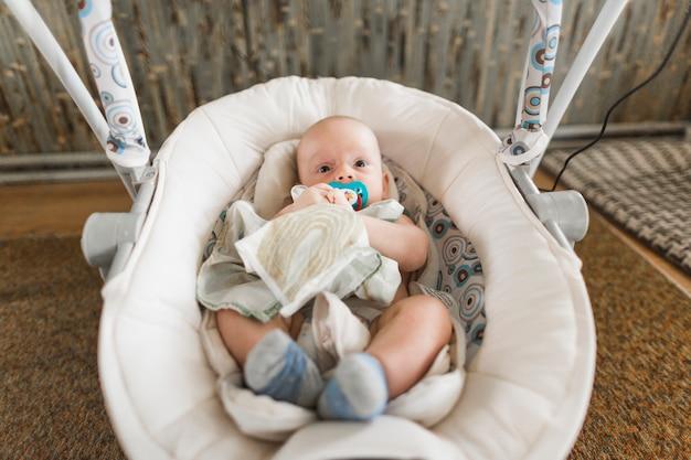 Nettes baby mit dem friedensstifter, der zu hause auf kinderwagen liegt Kostenlose Fotos