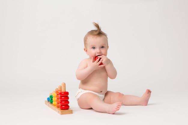 Nettes baby mit entwicklungsspielzeug auf einem weißen hintergrund Premium Fotos