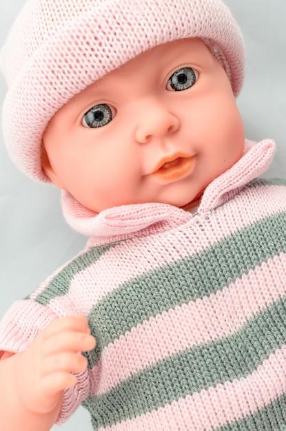Nettes baby - puppe für mädchen im strickkleidabschluß oben Premium Fotos