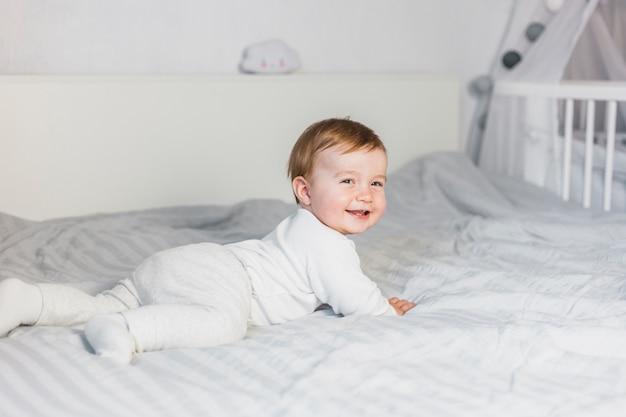Nettes blondes baby im weißen bett mit teddybären Kostenlose Fotos
