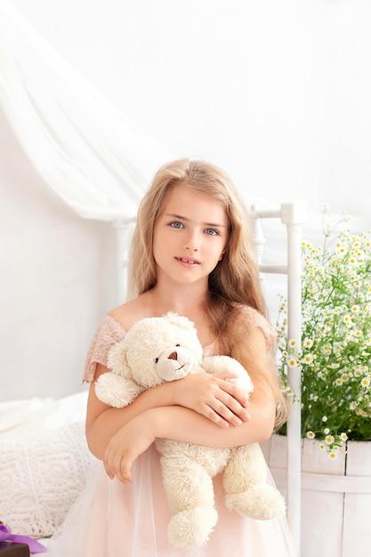 Nettes blondes kleines mädchen im kleid umarmt teddybär auf bett im schlafzimmer zu hause. kind, das ein spielzeug spielt. Premium Fotos