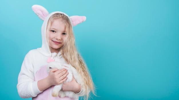 Nettes blondes mädchen in den häschenohren mit kaninchen Kostenlose Fotos