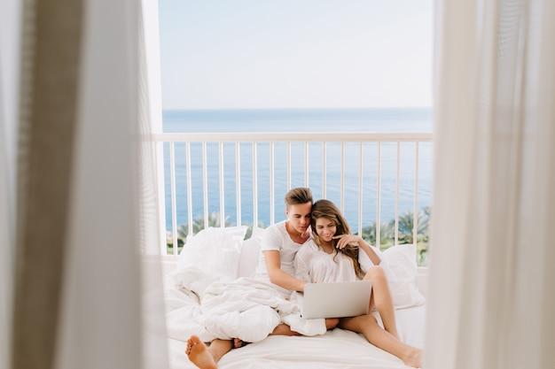 Nettes brautpaar in weißen kleidern, die auf bett sitzen und hochzeitsfotos auf laptop betrachten. porträt des fröhlichen kerls, der auf terrasse mit seiner herrlichen freundin mit vorhängen auf vordergrund ruht Kostenlose Fotos