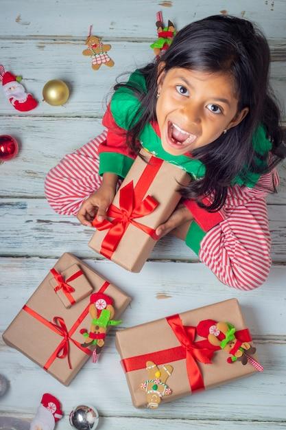 Nettes brunettemädchen mit ihren geschenken am weihnachtstag Premium Fotos