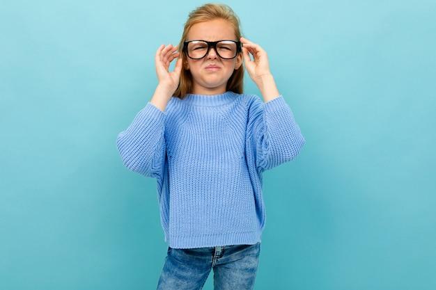 Nettes europäisches mädchen, das in den gläsern auf hellblau schielt Premium Fotos