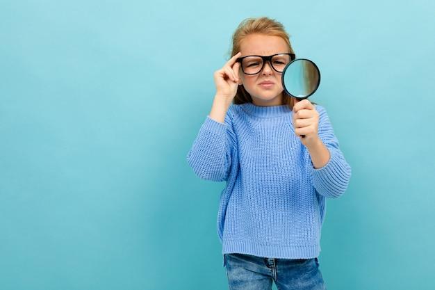 Nettes europäisches mädchen in den gläsern schaut durch eine lupe auf hellblau Premium Fotos