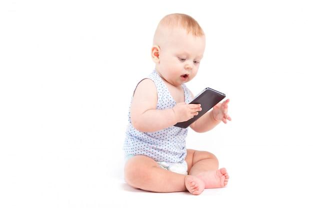 Nettes frohes baby im blauen hemd und in der windel halten mobiltelefon Premium Fotos