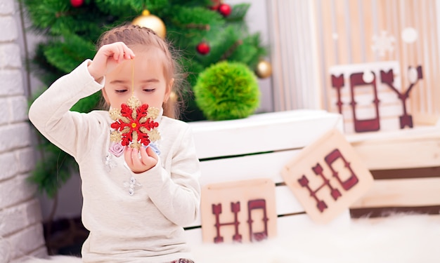 Nettes gelocktes kleinkindmädchen, das an einem weihnachtsessentisch vereinbart die teller sich vorbereitet, um weihnachtsabend zu feiern, ansicht durch ein fenster von der außenseite in ein verziertes esszimmer mit baum und lichtern steht Premium Fotos