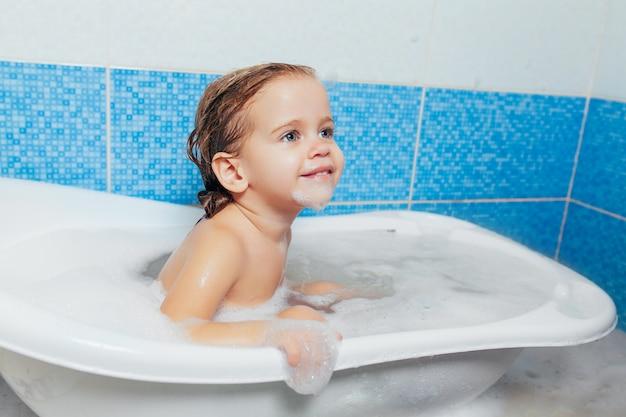 Nettes glückliches kleinkindbaby des spaßes, welches das bad spielt mit schaumblasen nimmt. Premium Fotos