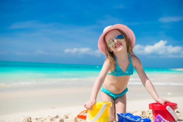 Nettes glückliches mädchen, das mit spielwaren auf strandferien spielt Premium Fotos