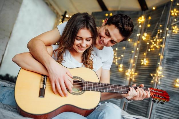 Nettes glückliches paar, das gitarre spielt Premium Fotos