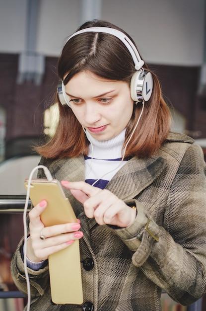 Nettes hübsches brunettemädchen in einem einkaufszentrum, das spaß hat, musik in den kopfhörern zu hören und musik von ihrem telefon auszuwählen Premium Fotos