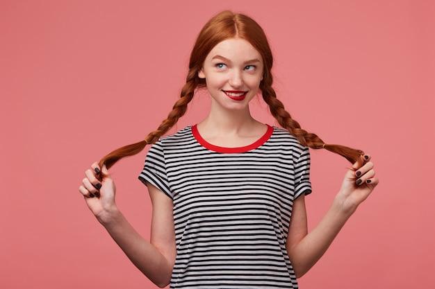 Nettes hübsches rothaariges mädchen mit roten lippen, die zwei zöpfe in den händen halten, gekleidet in abgestreiftem t-shirt, flirtend spielerisch betrachtend das linke obere eckplotterabenteuer isoliert Kostenlose Fotos