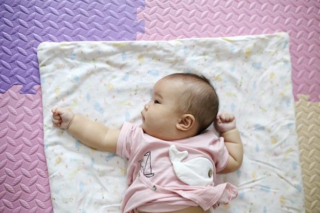 Nettes intelligentes asiatisches neugeborenes baby, das zu hause mit teddybärkaninchenspielzeug auf rosa weichem bett schläft. Premium Fotos
