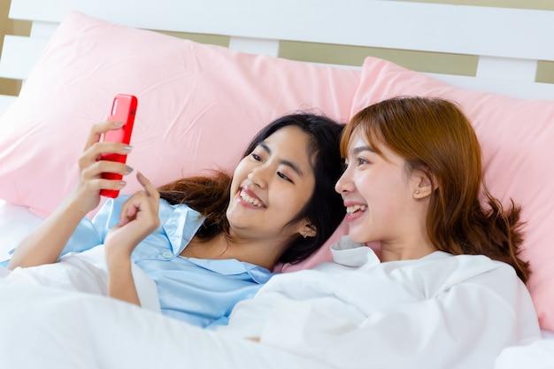 Nettes jugendlichfrauengebrauch smartphone selfie auf bett Kostenlose Fotos