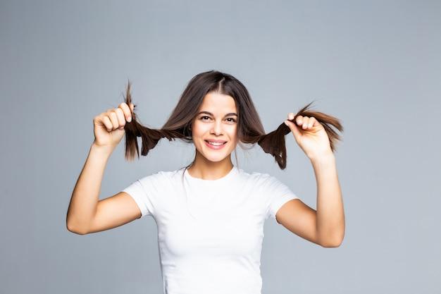 Nettes junges mädchen, das mit ihrem haar spielt, das auf grau isoliert wird Kostenlose Fotos