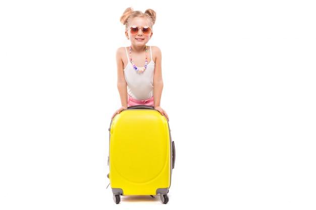 Nettes junges mädchen im weißen hemd, in den rosa kurzen hosen und in der sonnenbrille stehen nahe gelbem koffer Premium Fotos