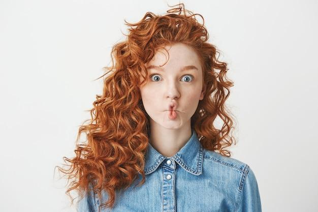 Nettes junges mädchen mit foxy lockigem haar, das lustiges gesicht macht. speicherplatz kopieren. Kostenlose Fotos
