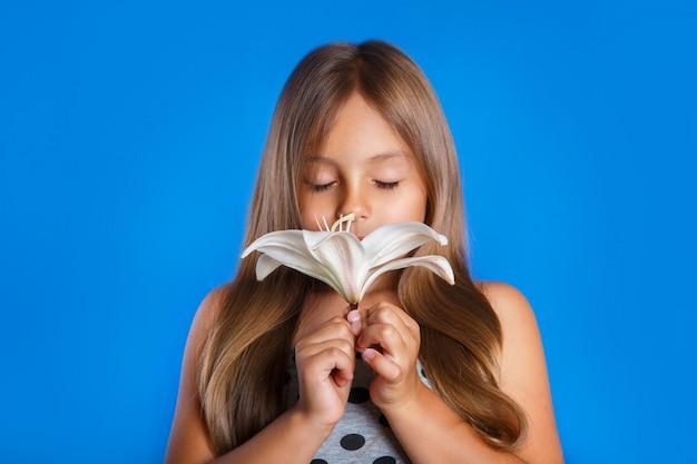 Nettes junges mädchen mit geschlossenen augen eine blume riechend Premium Fotos
