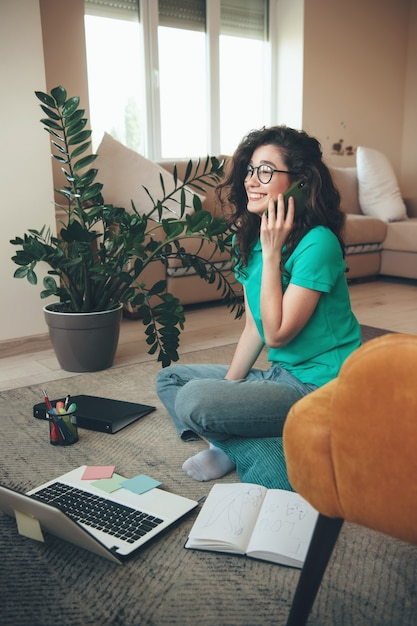 Nettes kaukasisches mädchen mit brille und lockigem haar, das am telefon spricht, während man auf dem boden sitzt und online-lektionen hat Premium Fotos