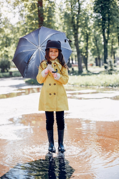 Nettes kind, das an einem regnerischen tag plaiyng ist Kostenlose Fotos