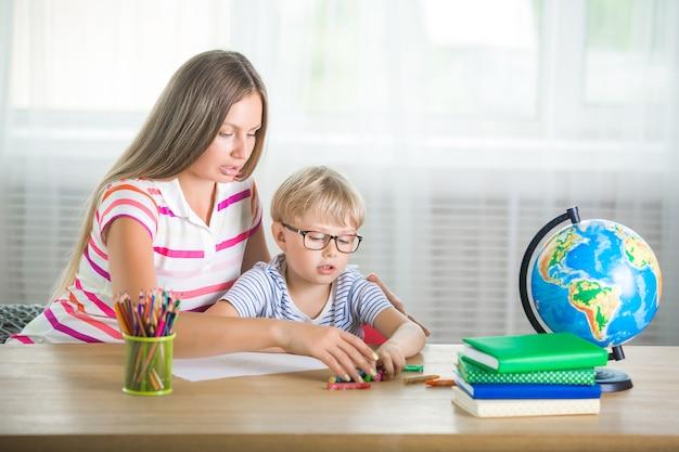 Nettes kind, das eine lektion mit seiner mutter lernt. familie, die zusammen hausaufgaben macht. mothe erklärt ihrem kleinen schüler, wie man eine aufgabe erledigt. Premium Fotos