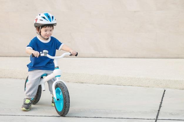 Nettes kind der nahaufnahme fahren fahrrad auf zementboden am parkplatz Premium Fotos