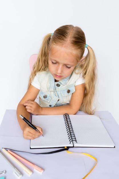 Nettes kind macht hausaufgaben auf weißem hintergrund. Premium Fotos