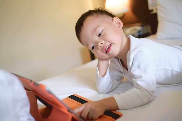 Nettes kleines asiatisches kleinkindjungenkind, das im bett sitzt und ein video vom tablet-pc sieht Premium Fotos
