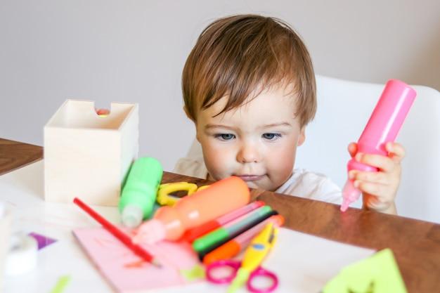 Nettes kleines baby, das rosa farbe in seiner hand betrachtet scheren auf tabelle hält. diy conc Premium Fotos