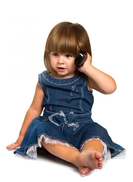 Nettes kleines baby spricht am handy, lokalisiert über weiß Premium Fotos