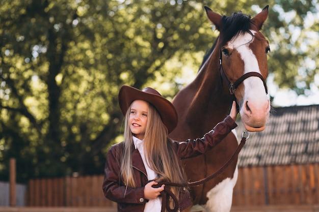 Nettes kleines blondes mädchen mit pferd an der ranch Kostenlose Fotos