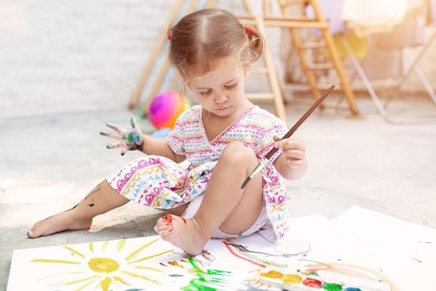 Nettes kleines kaukasisches mädchen, das das malen am hinterhof genießt Premium Fotos