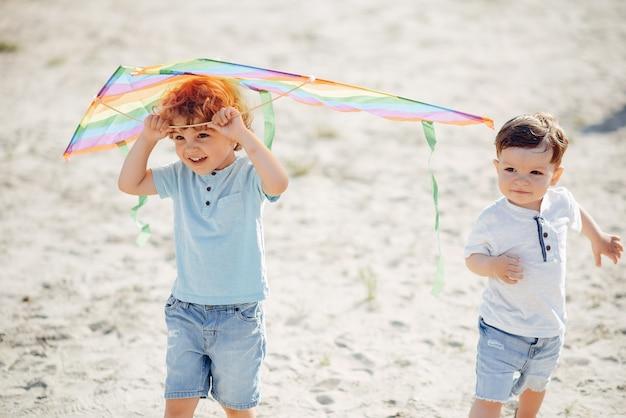 Nettes kleines kind auf einem sommergebiet mit einem drachen Kostenlose Fotos