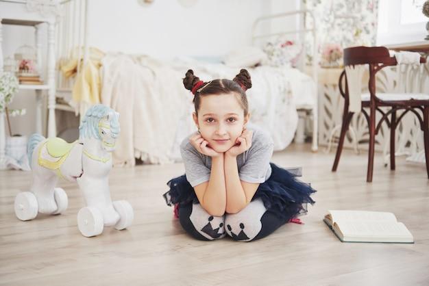Nettes kleines kindermädchen, das ein buch im schlafzimmer liest. kind mit krone sitzt auf dem bett nahe fenster Premium Fotos