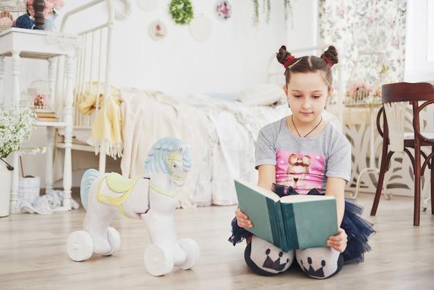Nettes kleines kindermädchen, das ein buch im schlafzimmer liest. Premium Fotos